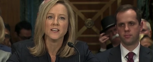 photo of Kathy Kraninger at Senate Hearing with Monopoly Man in background